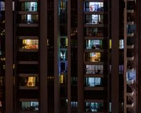 Toned background with night life in big city. Modern high-rise building with windows of cozy apartments in which light shines, people doing routine things stock image
