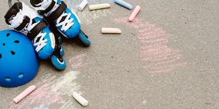 Toned baner Roller inline skates in skate park on gray urban background with colorfull crayons Stock Images