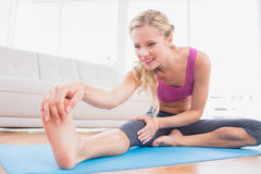 Toned blonde stretching on exercise mat Stock Photos