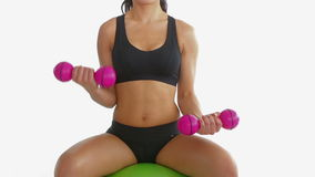 Toned brunette sitting on exercise ball training with dumbbells. On white background stock video footage