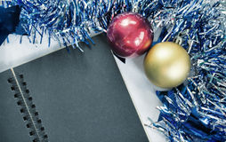 Toned Christmas background photo. Blank page of black notebook. Blue ribbon wreath. Stock Image