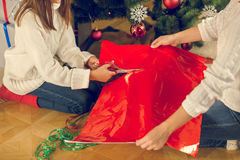 Toned closeup of girl and mother sitting under Christmas tree an Stock Photo