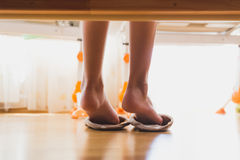 Toned closeup photo of girl putting on slippers after waking up stock photography
