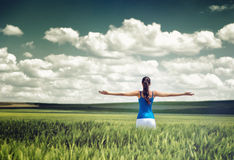 Toned dramatic image of a girl in a wheat field. Standing looking away from the camera with outspread arms as she rejoices her freedom and the beauty of the Royalty Free Stock Photo