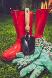 Toned filter of garden tools and red boots on meadow Stock Image