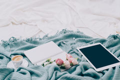 Toned Flat lay tablet, phone, cup of coffee and flowers on white blanket with turquoise plaid. Toned Flat lay tablet and flowers on white blanket with turquoise Royalty Free Stock Image