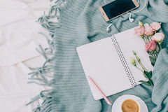 Toned Flat lay tablet, phone, cup of coffee and flowers on white blanket with turquoise plaid. Toned Flat lay tablet and flowers on white blanket with turquoise Stock Photo
