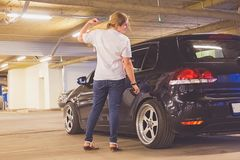 Toned. Girl in a white T-shirt and jeans polishes her car indoors. Copy space on the back stock photography