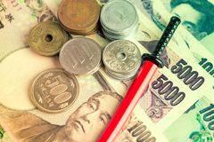 Toned illustrative editorial of Japanese Yen in notes and coins and a miniature katana in red scabbard.  royalty free stock image