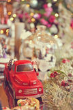 Toned image of Adorable christmas red car toy with santa and presents. Musical miniature decoration on tree bokeh stock photography