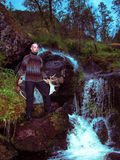 Toned image of an adult male in sweater standing near a creek with antlers on the background of rocks Stock Images