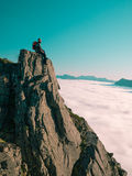 Toned image adult man with backpack sitting, legs dangling on the edge of a cliff and looks into the distance against the blue sky Stock Photos