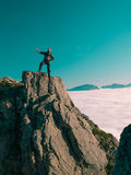 Toned image adult man with backpack stands on the edge of a cliff and looks into the distance against the blue sky Stock Photos