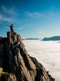 Toned image adult woman with a backpack with arms outstretched stands on the edge of a cliff and looking at the sunrise against th Royalty Free Stock Photography