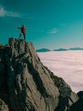 Toned image adult woman with a backpack with arms outstretched stands on the edge of a cliff and looking at the sunrise against th Royalty Free Stock Photo