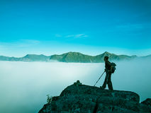 Toned image of an adult woman standing on top of a mountain with a backpack and Alpenstocks against mountains in a fog Royalty Free Stock Images