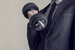 Toned image of a businessman doing dumbbell biceps curl. Retro effect faded and toned image of a businessman doing dumbbell biceps curl wearing a formal suit Stock Photography
