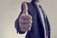 Toned image of businessman showing a thumbs up sign towards you Stock Image