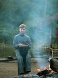 Toned image of the child sitting on the bench and playing a drum next to a burning fire Stock Photography
