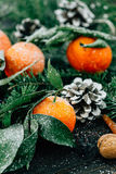 Toned image Christmas composition with snowy Tangerines, Pine cones, Walnuts on Wooden Background, holiday decoration Royalty Free Stock Photography