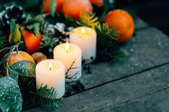 Toned image Christmas composition with Tangerines, Pine cones, Walnuts and Candles on Wooden Background, holiday decoration Stock Images