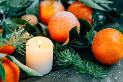 Toned image Christmas composition with Tangerines, Pine cones, Walnuts and Candles on Wooden Background, holiday decoration Royalty Free Stock Images