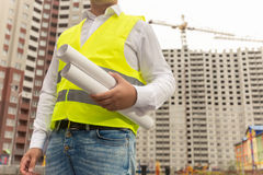 Toned image of construction engineer holding blueprints. Closeup toned image of construction engineer holding blueprints Royalty Free Stock Photography