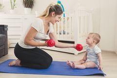 Toned photo of cute smiling baby boy looking at mother sitting on fitness mat and practicing fitness. Toned image of cute smiling baby boy looking at mother Royalty Free Stock Images