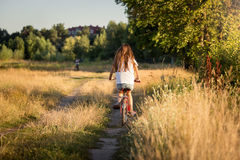 Toned image of girl riding bike at fields at sunset Royalty Free Stock Image