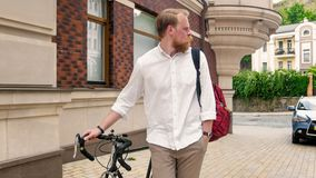 Toned image of handsome bearded man walking with bicycle on street. Toned photo of handsome bearded man walking with bicycle on street Royalty Free Stock Photos