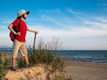 Toned image of a little boy with a backpack and a hat that holds the stick and standing on a sandy hill against the background of Stock Photos