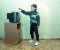 Toned image of a little boy with a disappointed face which is holding the TV remote royalty free stock photography