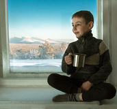 Toned image of a little boy sitting on an old window sill next to the window and holding in his hand a metal cup against the backg Stock Photos