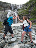 Toned image married couple of tourists standing on rocks and holding hands. On a background of a high mountain with a waterfall Stock Photo