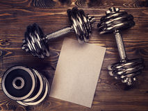 Toned image of metal dumbbells and a sheet of craft paper Royalty Free Stock Photography