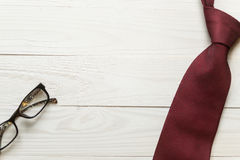 Toned image of necktie and eyeglasses lying on white wooden back Stock Photo