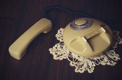 Toned image of an old-fashioned phone on knitted napkin on a dar Royalty Free Stock Image