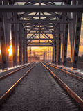 Toned image of the railway with sleepers and rail bridge on a background of multicolored sunset Stock Image
