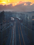 Toned image of the railway with sleepers and rail bridge on a background of multicolored sunset Stock Photography