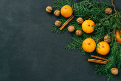 Toned image rustic eco christmas composition tangerines, nuts, cinnamon sticks and natural cypress branches on bark background royalty free stock images