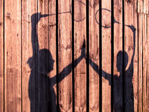 Toned image of silhouettes of men and women holding hands with tennis rackets Royalty Free Stock Photography