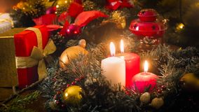 Toned image of three burning candles, gifts and wreath on Christmas eve Stock Photos