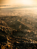 Toned image view from the window of an airplane to the Chinese mountains in winter on a background of sunset Royalty Free Stock Photos