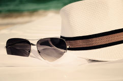 Toned image white hat and sunglasses on the background of sea an Royalty Free Stock Image