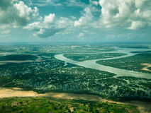 Toned image from the window of an airplane of the river and wetland forest with the city of Mombasa in the background with the sky Stock Images