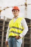 Toned photo of young man in white shirt and hardhat standing on building site. Toned image of young man in white shirt and hardhat standing on building site Royalty Free Stock Photo