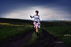 Toned image of young woman running on a countryside road Stock Image
