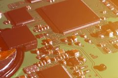 A toned macro image of a computer board with many small technological elements. Extremely shallow depth of field. Abstract techno. Logical background stock photo