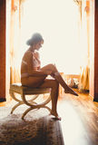 Toned photo against window of elegant woman sitting on chair Royalty Free Stock Photo