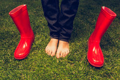 Toned photo of barefoot girl posing with red gumboots on meadow Stock Photography